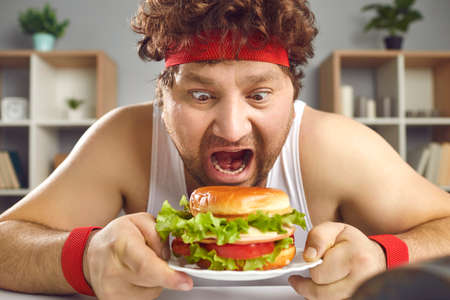Hungry crazy chubby man in sportswear sitting at table and eating fast food hamburger. Overweight male person junk meal lover with opened mouth widely closeup portrait. Diet failure, cheat-meal Фото со стока