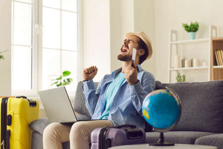 Online travel agency concept. Young happy excited male traveller in hat screaming doing winner gesture clenching fists say yes holding passport with flight tickets sitting front of laptop on home sofa