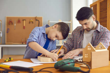 Concentrated father and son building wooden birdhouse spend time together. Caucasian family at carpentry workshop. Home leisure activity, educational entertainment and parent pastime with children
