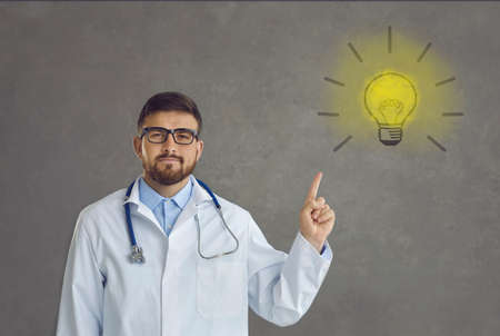Studio portrait of proud handsome professional doctor in white lab coat pointing at yellow light bulb symbol. Concept of idea, innovation, finding new medical solutions and effective treatment methods
