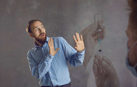 adult man waves his arms, feeling great fear of being injected with the vaccine against Covid-19. Man is afraid of doctors mistakes and therefore refuses to be vaccinated. Gray background. Banner.