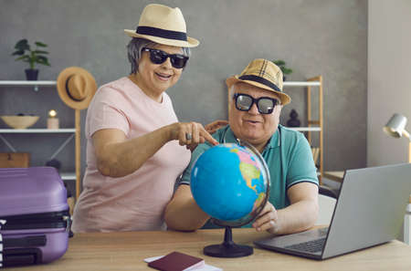 Happy excited retired senior couple planning holiday trip together. Cheerful old people in hats and sunglasses choosing their dream destination on Earth globe. Traveling and active vacation concept
