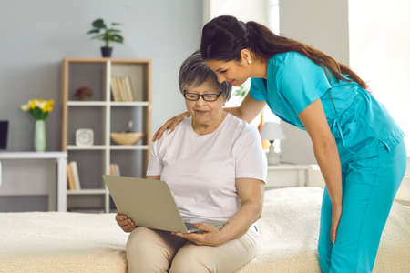 Professional care service hospital help hand for pensioner. Woman nurse teach elderly lady patient use internet social media or browser search on laptop. Caregiver and aged female at home