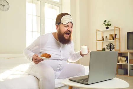Happy man sitting on bed at home, having morning coffee, watching funny movie on laptop and laughing. Plus size guy eating breakfast and enjoying new situation comedy episode on online video platform