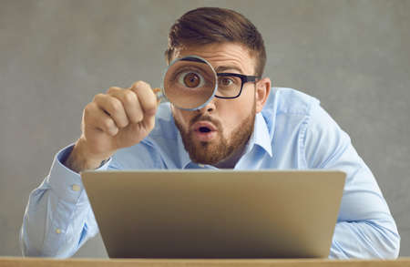 Portrait of funny handsome nerd young business man in glasses sitting at office desk with laptop computer, holding magnifying glass and looking at something with big eye and surprised face expression