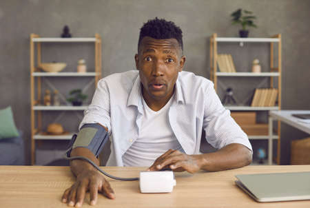 Videocall headshot of sick black man shocked after measuring high blood pressure. Webcam videoconference view of young African American patient with hypertension sitting at table and looking at camera