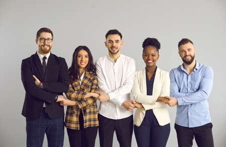 Group of five happy smiling millennial business people and startup company colleagues standing in row, holding hands and looking at camera. Team, teamwork, corporate support, work community concept Imagens