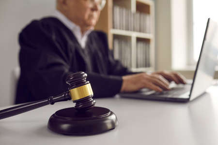Close up of dark brown gavel on table on background of senior male judge working on laptop. Concept of law, justice, fairness and online legal advice. Blurred background. Reklamní fotografie