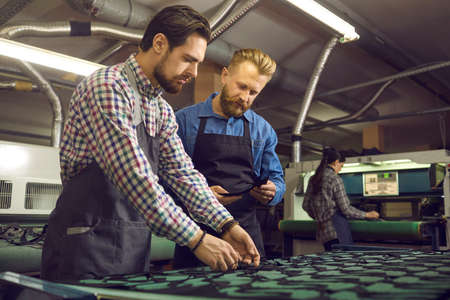 People working at a shoe factory. Manufacturing workshop manager checking the quality of work of his employee. A more experienced master helping his new trainee with shoe cutting patterns