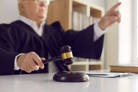 Close up of a hammer blow made by a mature judge passing sentence and announcing the closure of the case. Concept of judicial verdict, legal justice and fair trial. Banque d'images