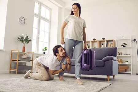 Young couple breaking up. Woman with packed bag leaving home. Funny clingy traitor husband on floor holding wifes leg imploring her to give second chance. Relationship breakup and divorce concept
