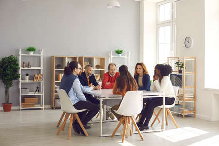 Team of mixed race business people sitting around big table in modern office space. Group of diverse company employees discussing projects and taking decisions together in corporate meeting Stock fotó