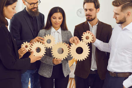 Young company managers joining gearwheels as metaphor for effective management and collaboration