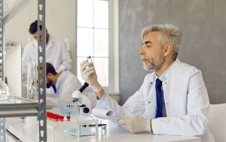 Mature scientist sitting at table and looking at new vaccine in glass vial hes holding. Serious old man in lab coat and gloves doing research in advanced medical laboratory Stock fotó