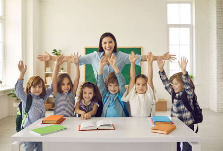 Happy teacher with arms widely spread to hug cheerful children raising hands. Positive portrait in classroom. Educator showing love, adoration and care for pupils. Children and tutor looking at camera Foto de archivo
