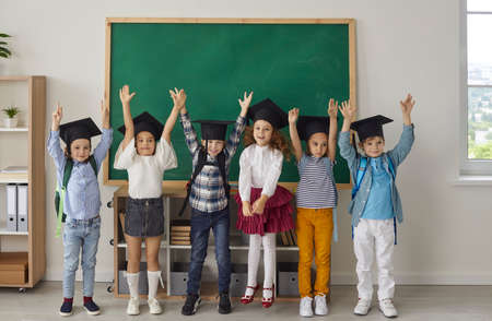 Kids graduate. Portrait of funny little kindergarten or junior high school graduates who are dressed in mortar boards. Kids having fun in the classroom on the background of the school board.