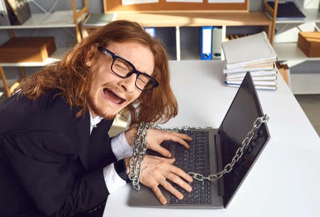 Desperate corporate slave stuck in the office. Tired employee sitting at desk chained to laptop computer and crying unable to go home. 9 to 5 job, technology addiction, working extra hours concept Foto de archivo