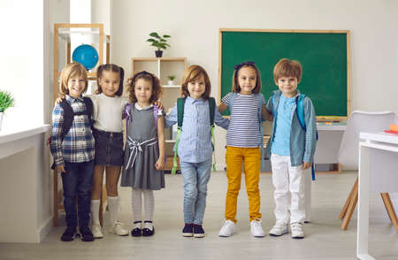 Group portrait of happy cute little children at school or kids educational centre. Small group of elementary students standing in the classroom, smiling and looking at the camera. Education concept