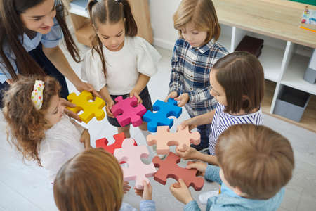 Team of little school children with teacher standing in circle and joining colorful jigsaw puzzle pieces trying to fit them together, high angle close up. Education, fun, teamwork in classroom concept Standard-Bild