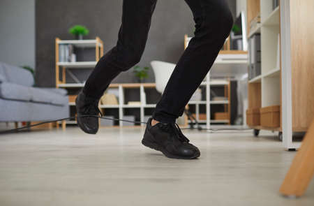 Man in uncomfortable sneakers trips over power cable at home. Closeup male worker in black shoes stumbles over electric cord in office. Close up shot feet stepping on floor. Domestic accident concept