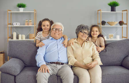 Portrait of a happy grandmother, grandfather and their two little granddaughters. Twin sisters are standing behind grandparents who are sitting on the couch and looking at the camera smiling. Stock Photo