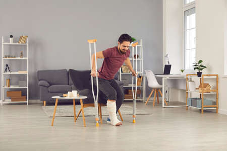 Rehabilitation and recovery of people after physical injury such as bone fracture in car accident: Man with broken leg in plaster cast trying to stand up from chair and to walk with crutches at home