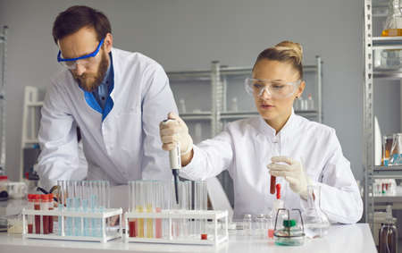 Team of focused scientists working together on sample analyzes while working in a lab. Male scientist makes notes while his female assistant uses a pipette to add liquid to one of several test tubes.