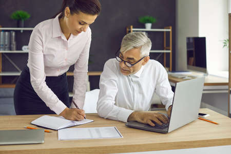 Two serious people working in modern office. Senior executive and young personal assistant planning schedule, discussing future events and meetings, making arrangements and organizing business process Standard-Bild