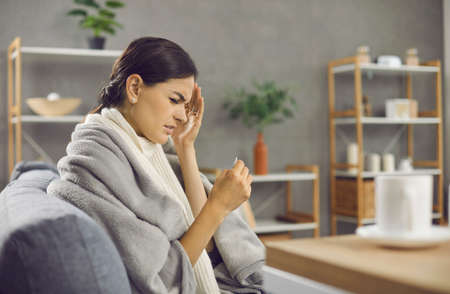 Sad unhappy lady who has seasonal flu or cold fever taking her temperature and drinking warm tea. Sick woman wrapped in warm blanket or plaid sitting on sofa at home and looking at thermometer in hand Standard-Bild