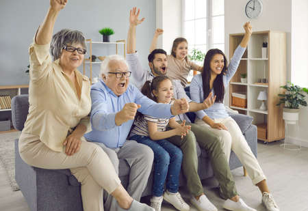 Fun from grandparents to children. Excited happy big family of different generations watching football match on sofa at home. Older and younger fans emotionally encourage their favorite team.