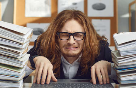 Unhappy tired employee doing paperwork and working on laptop computer. Portrait of funny sad helpless miserable overworked office worker sitting at desk and crying stressed by all the paper workload