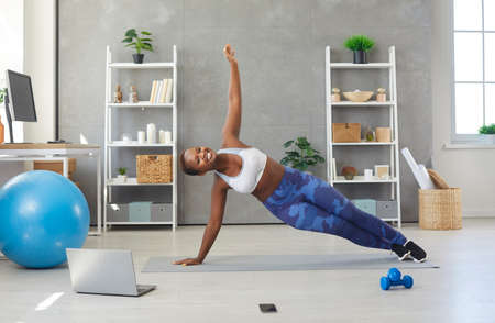 Portrait of smiling young African American woman in sportswear make plank do morning exercises gymnastics online at home. Happy millennial ethnic female train on video webcam call on laptop.