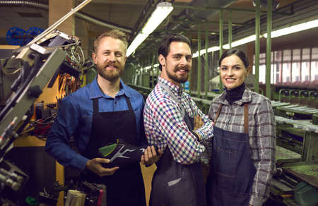 Portrait of three happy proud satisfied young shoe factory workers standing together in assembly line workshop, smiling and looking at camera. Footwear manufacturing industry concept
