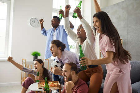 Group of young multiracial male and female football fans watching match on TV, drinking beer and supporting favourite team. Excited multiethnic friends shouting hoping favorite soccer team scores goal