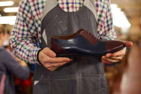 Cropped shot of a shoe factory worker holding a new shiny stylish black and brown male leather boot in hands. Concept of leather footwear manufacturing industry Standard-Bild