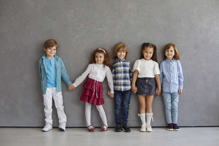 Portrait of cute and happy little boys and girls in casual clothes standing against the gray wall. Beautiful smiling and funny kids standing in a row holding hands. Childhood concept.