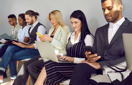 Different diverse multiethnic mixed race business people in smart casual clothes holding laptops, using cellphones, reading papers, documents, CVs and resumes while waiting in line for job interview Standard-Bild