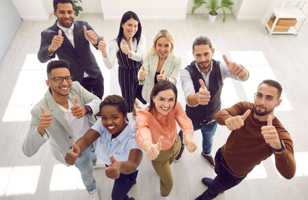Diverse team of happy motivated young mixed race business people standing in office, looking up, smiling and giving thumbs up all together. High angle, from above, top view. Teamwork, success concept Standard-Bild
