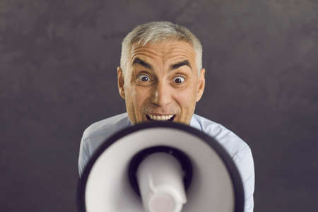 Close up portrait of middle-aged Caucasian man isolated on black background scream about good sale deal in speaker. Male hold loudspeaker megaphone announce promotion or discount offer to client. Standard-Bild