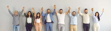 Team of successful business people of different ages holding hands and smiling. Banner with group portrait of happy motivated multi aged men and women standing together against grey studio background