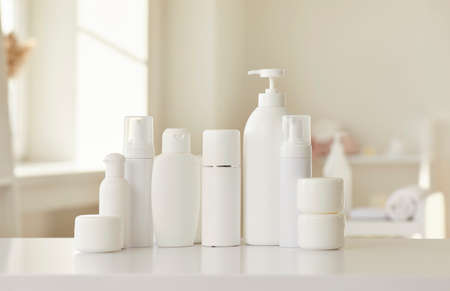 Cosmetic skin care products of new female bodycare line for health, beauty and wellbeing. White mockup lotion bottles, cream jars and soap dispenser standing in row on table or shelf in beauty parlour Standard-Bild