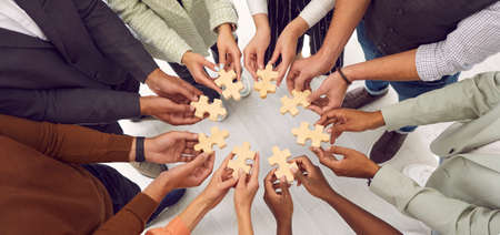 Banner background with multiethnic group of young people standing together and joining pieces of jigsaw puzzle as metaphor for business team and teamwork. Cropped shot of hands holding jigsaw parts Standard-Bild