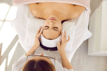 Young woman on examination bed or massage table getting rejuvenating cosmetic facial procedure for fresh perfect skin done by skin care professional at beauty salon or spa room. Top overhead view Standard-Bild