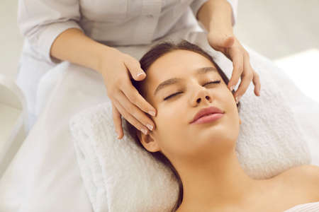 Close up of cosmetologist make face lifting massage to woman client in beauty salon. Dermatologist do facial skincare procedures for healthy glowing skin for female patient. Cosmetology concept.
