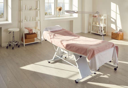 Beautiful interior of new massage salon, spa room, beauty parlour, or dermatological clinic with empty bed covered with towels, magnifying lamp, and modern skin care products on shelves and wall racks