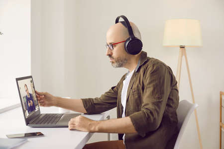 Serious focused bald man wearing headphones and glasses sitting at modern laptop in home office, discussing work at casual online telework videocall meeting with boss or corporate manager, side view
