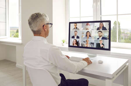 Mature man sitting at office desk, looking at computer screen and holding online video call staff meeting with international business team of senior and young Caucasian and Middle Eastern coworkers