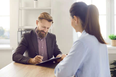 Client signing papers. Happy smiling handsome bearded young man in suit sitting at office desk with female business assistant, bank manager or insurance agency worker and putting signature on contract