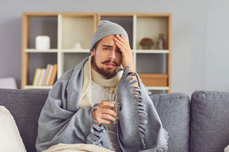 Person on self-isolation at home. Sick man with a glass of water in his hand suffers from a great headache sitting at home on the couch. Guy sitting in a warm sweater, hat and wrapped in a blanket.