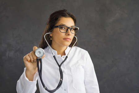 Young serious female healthcare worker holding a stethoscope extended towards the viewer. Close up of female doctor in glasses listens to heartbeat while standing on gray background. Standard-Bild